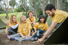 Cheerful Children Looking At Camp Counselor Tapping Tent Peg In Ground
