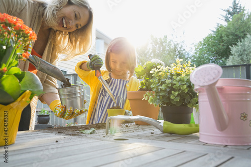 Grandmother potting plants with granddaughter in backyard