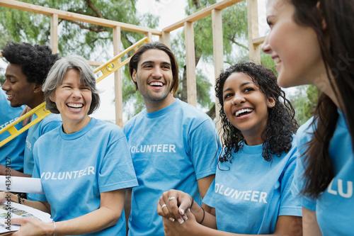 Fotografering Happy team of volunteers at construction site