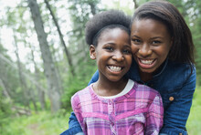Portrait Of Happy Sisters Standing Together In Forest