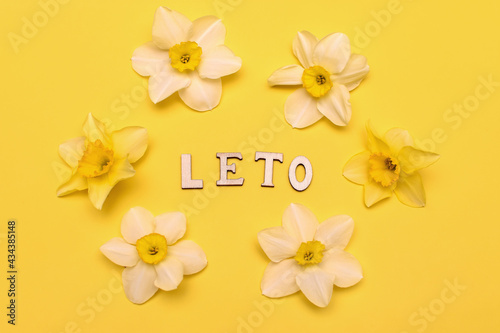 Leto lettering in English letters on a yellow background. The Russian word summer, written in English letters, is laid out in wooden letters.