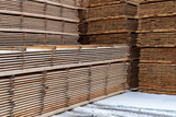 Large Stacks Of Wooden Planks Background With Selective Focus. Winter Woodwork Industrial Storage.