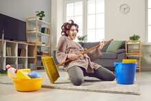 Funny Housewife Who Cleans The House, Sings And Plays On A Broom, As If On An Imaginary Guitar. Cheerful Woman In Hair Curlers, Bathrobe And Face Mask Fooling Around And Having Fun.