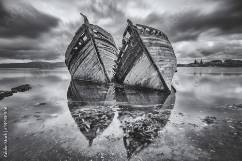 Fototapeta Reflection Of Clods And Two Wrecked Boats Abandoned On The Shore