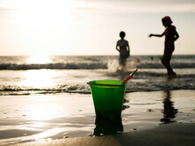 Close-up Of Bucket On Beach With Kids Playing At Beach