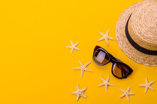 Beach Accessories: Glasses And Hat With Shells And Sea Stars On A Colored Background