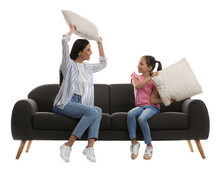 Young Woman And Her Daughter Having Pillow Fight On Comfortable Grey Sofa Against White Background