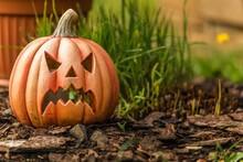 Pumpkin Shaped Ceramic Candlestick On Green Grass. Funny Carved Pumpkin In The Garden, Halloween Background