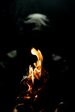 Vertical Shot Of A Person Holding A Fire Torch In The Dark