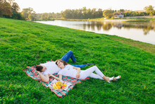 Top View Of Relaxed Man And Woman Lying In The Park With Appetizing Fresh Fruits. Couple On A Picnic Lies On A Blanket In The Grass Outdoors.