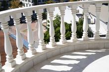 White Balustrade On Balcony On Summer Sunny Day Close Up. Railing Shadow.