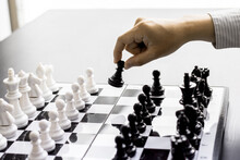 A Man Picking Up Black Chess On A Chessboard.