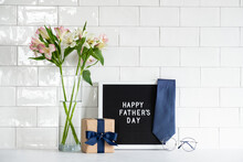 Happy Fathers Day Concept. Festive Composition With Gift Box Wrapped Craft Paper With Blue Ribbon, Letterboard With Text Happy Father's Day, Necktie, Boquet Of Flowers, Glasses.