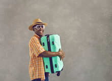 Happy African Man Going On Summer Vacation. Portrait Of Cheerful Black Tourist In Sunglasses, Sun Hat And Orange Shirt Smiling And Holding Mint Green Travel Suitcase Standing On Gray Studio Background