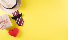 Happy Father's Day Background Concept With Tie And  Mustache, Hat, Gift Box, Red Heart  On Pastel Yellow Background.