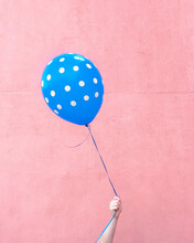 Hand Holding Blue Balloon In Front Of Pink Wall