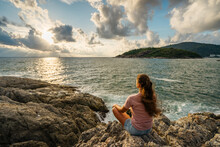 Young Woman Meditating At The Seaside Sitting In The Lotus Position On Rocks Overlooking The Sea With Sunset In A Healthy Lifestyle Concept