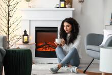 Beautiful Woman Drinking Tea Near Fireplace At Home