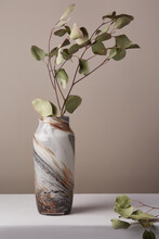Still Life Photo Of Branches With Green Leaves Placed Into Marble Vase Made In Technique Of Agate Glass. The Designer Vase Is Located On White Table Against Gray Wall.