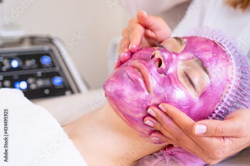 Cosmetologist making  massage the skin of the forehead. Woman in a spa salon on cosmetic procedures for facial care. Beautician applies a woman a therapeutic cream on her face. .