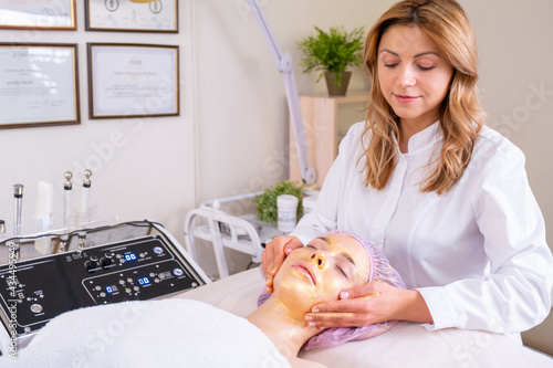 Cosmetologist applies a woman a therapeutic mask on her face. Woman in a spa salon on cosmetic procedures for facial care. Doctor does a massage of the girl's face with a moisturizing mask on a face..