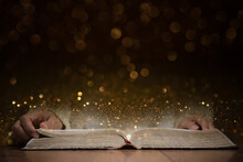 A Person Reading A Holy Bible With Gold Background.