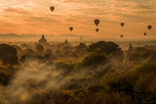 Hot Air Balloons Over Temples Of Bagan, Myanmar At Sunrise On A Misty Morning.
