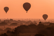 Three Hot Air Balloons Fly Over Many Temples Of Bagan, Myanmar At Sunrise.