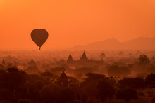 Single Hot Air Balloons Flies Over Temples Of Bagan, Myanmar At Sunrise With Warm Orange Sky.