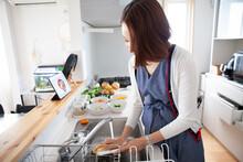 タブレットを見ながら自宅のキッチンで料理をする主婦