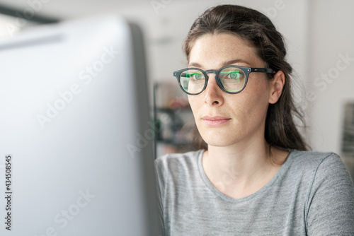 Woman with glasses working on a computer Fotobehang