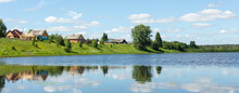 Typical Russian Landscape. Russian Village On The Shore Of The Lake. Panoramic Photo