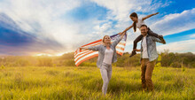Patriotic Holiday. Happy Family, Parents And Daughters Children Girl With American Flag Outdoors. USA Celebrate 4th Of July.