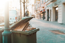 Full Paper Trash Can In The Pedestrian Zone At Beautiful Sunset - Environment, Recycling Concept. Paper And Cardboard Trash