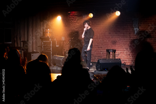 Young Caucasian male comedian performing his stand-up monologue on a stage of a Fototapet