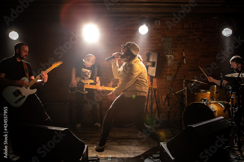 Canvastavla WIDE Punk rock band playing music during their concert on a stage of small venue