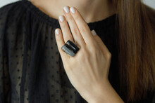 Beautiful Stylish Woman With Modern Square Black Ring On Hand And White Manicure, Closeup. Fashionable Female In Black Dress With Unusual Fused Glass Accessory. Beauty And Care.