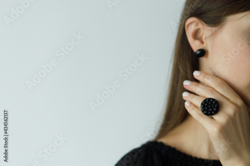 Fotografering Beautiful stylish woman with modern round black ring and earring, space for text
