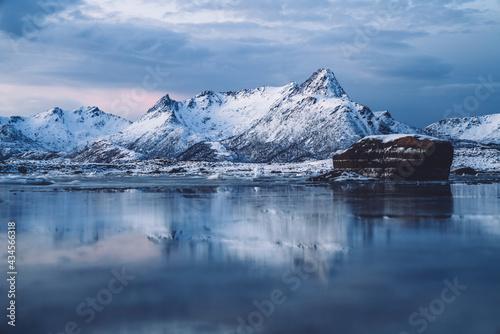 Snowy mountainous terrain with frozen sea at sunset