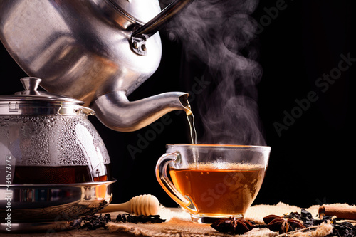 Canvastavla Tea ceremony process Tea ceremony A freshly brewed cup of black tea is placed on a wooden table where a warm soft light shines against a dark black background