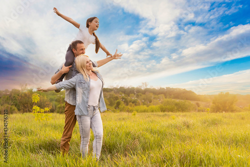 Fotografia Happy family: mother father and child daughter on nature on sunset