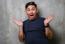 Young Japanese Man Wearing T-shirt Standing Over Concrete Wall Background Afraid And Shocked