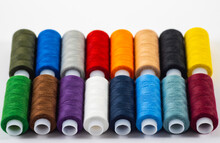 Several Multi-colored Bobbins With Thread Isolated On White Background.