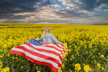 Adult Woman Holding American Flag With Pole, Stars And Stripe In A Yellow Rapeseed Field. USA Flag Fluttering In The Wind