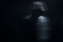 A Man In A Hood Stands On A Black Background