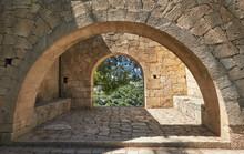 Arcadi Monastery In Crete, Greece, Stone Arches In Monastery Lush Green Garden