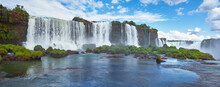 Iguazu Waterfalls In Argentina, View From Above. Panoramic View Of Many Majestic Powerful Water Cascades With Mist. Panoramic Image With Reflection Of Blue Sky With Clouds.