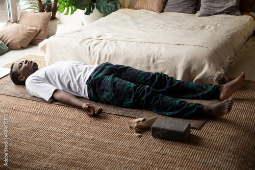 Young black man lying in Dead Body exercise or Corpse pose with his eyes closed, Fotobehang