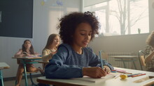 Girl Sitting At Desk In Classroom. Cheerful Student Writing In Notebook