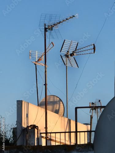 luz del atardecer reflejándose sobre antenas parabólicas. Fotobehang